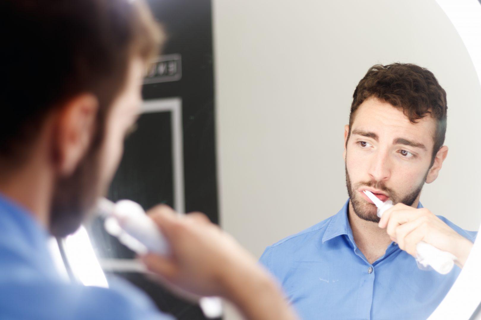 Chico lavándose los dientes frente al espejo