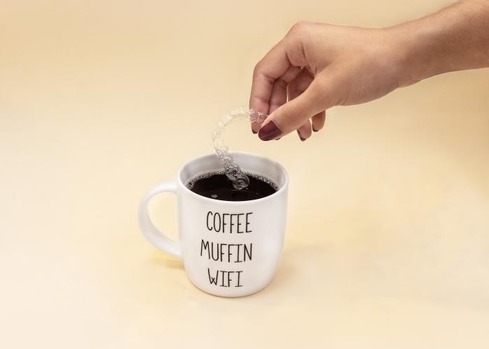 Mano mojando una ortodoncia invisible en café