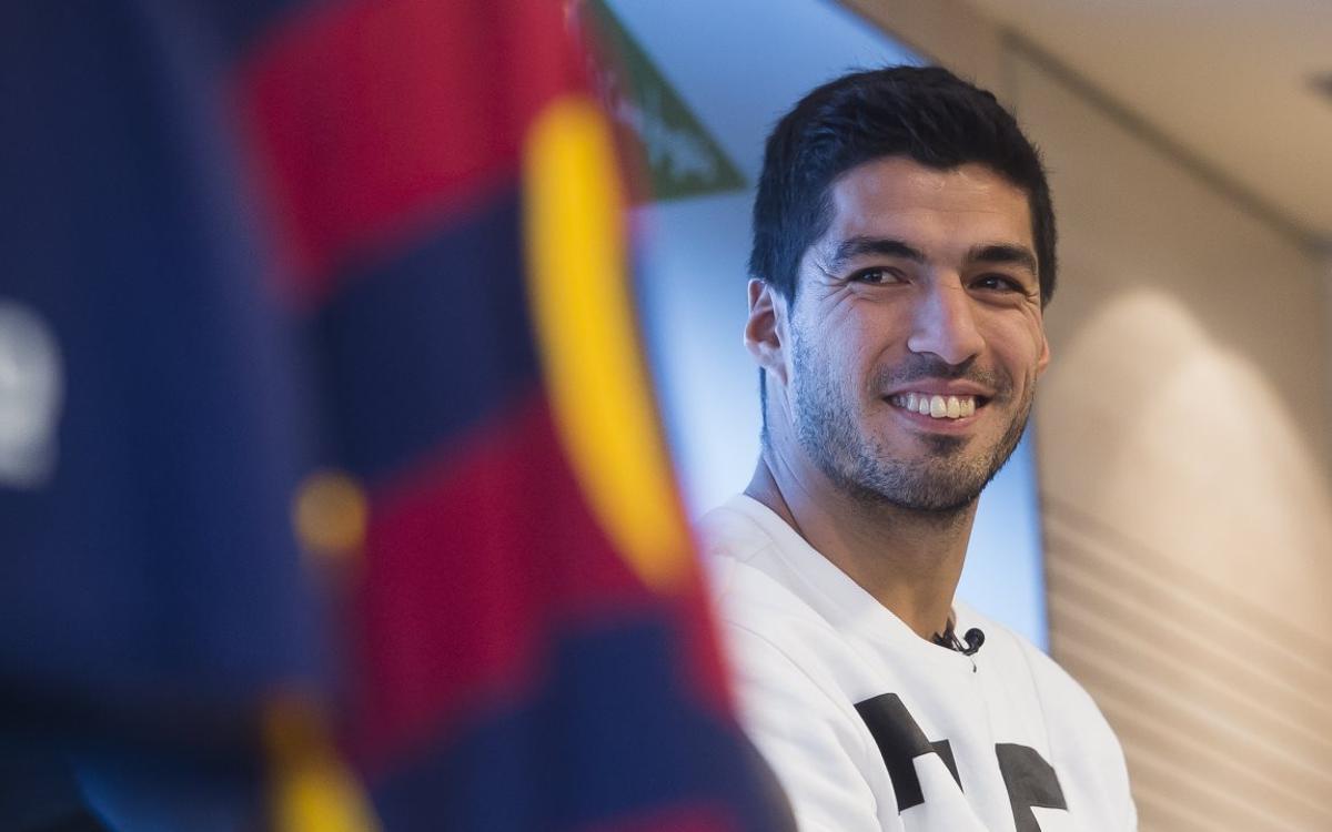 Luis Suárez junto al escudo del FC Barcelona